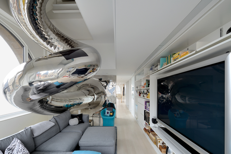 Metallic-tubular-slide-exit-into-living-entertainment-in-white-and-grey